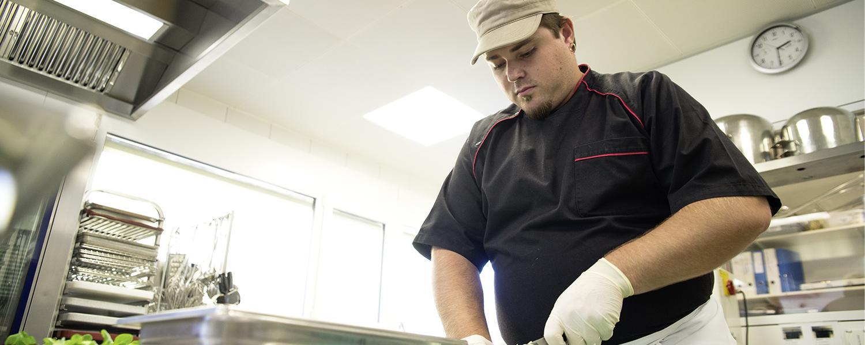 Koch in der Küche der Stiftung arwole